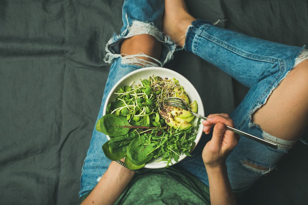 Healthy people don't diet. Woman eating a vegan bowl with quinoa, spinach, avocado, and greens.