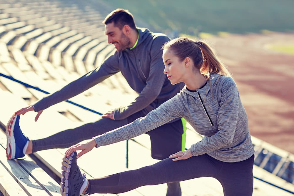 9 habits of healthy people. 1 man and 1 woman stretching after working out.