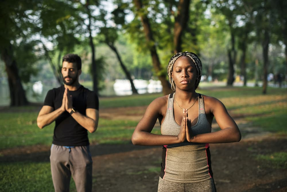Healthy people aren't stressed. 2 people in a park doing meditation and yoga.